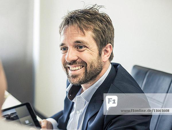 Over shoulder view of two businessmen at office desk using digital tablet