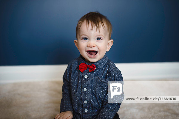 Portrait of male toddler in red bow tie sitting on floor