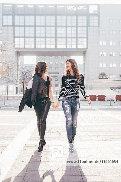 Zwillingsschwestern  draußen gehen  Händchen haltend