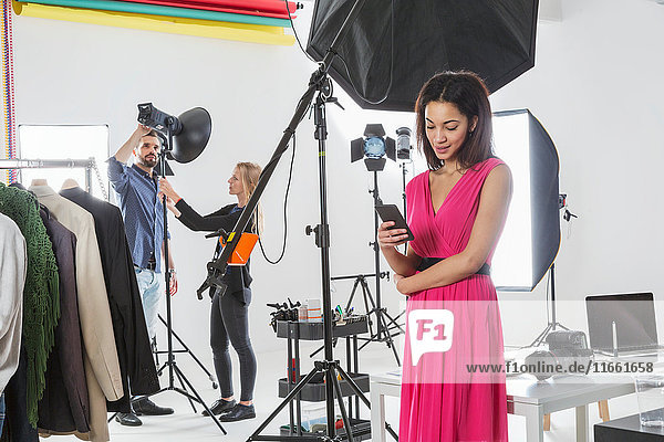 Young female fashion model looking at smartphone in photography studio