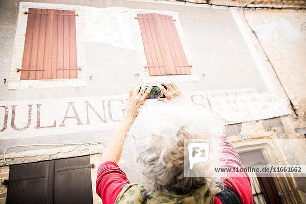 Frau fotografiert die Beschilderung an der Gebäudeaußenseite  Bruniquel  Frankreich
