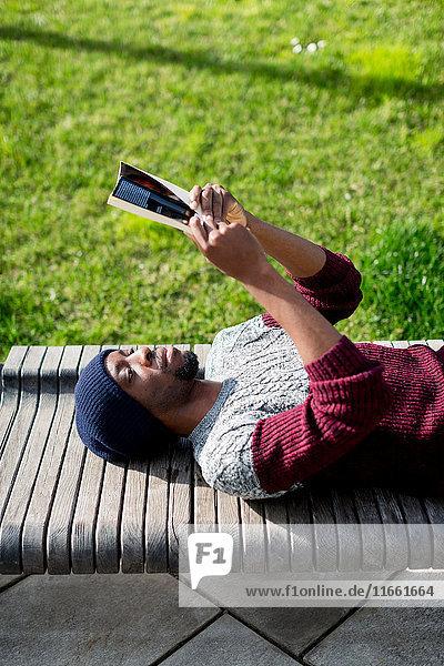 Man lying on bench  reading book
