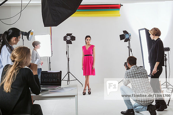 Photography team and model in white backdrop photography studio shoot