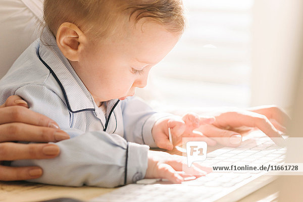 Mother typing with baby looking interested in keyboard