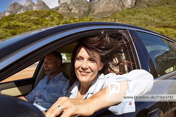 Couple in car  driving along rural road  woman leaning on open window