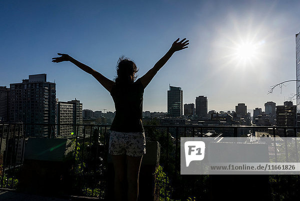 Woman with arms raised looking at view of Santiago de Chile  Chile