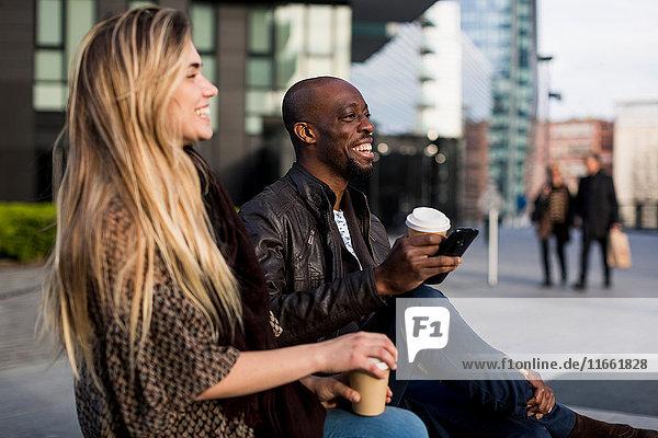 Glückliches junges Paar beim Kaffee zum Mitnehmen in der Stadt