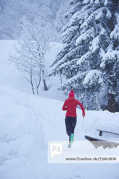Rückansicht einer Läuferin  die im Tiefschnee auf der Bahn läuft  Gstaad  Schweiz