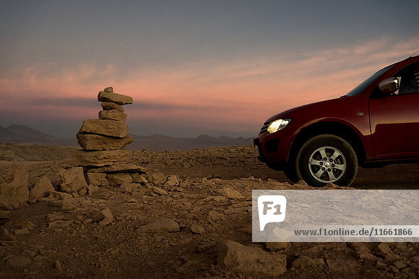 Car by stack of balanced rocks at sunset  San Pedro de Atacama  Chile