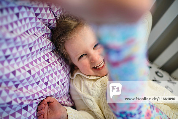 Lachendes Mädchen beim Spielen im Tagesbett