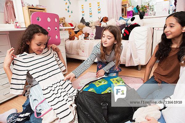 Mädchen im Schlafzimmer schauen auf Kleidung