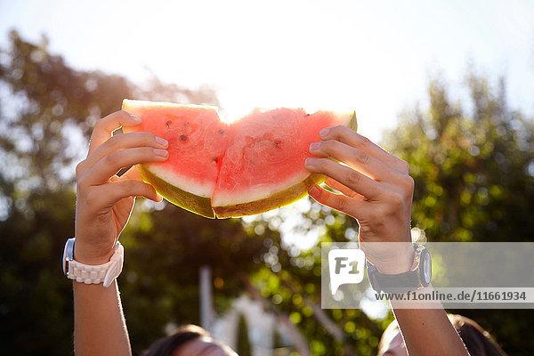 Teenager-Mädchen halten Wassermelone auf der Straße hoch