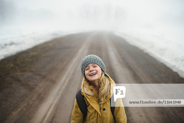 Portrait of girl in knit hat standing in middle of foggy dirt road laughing