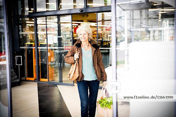 Reife Frau verlässt Supermarkt mit Einkaufstüte