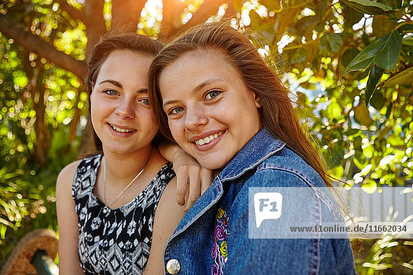 Portrait of two female friends in rural setting  smiling