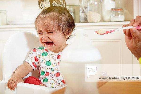 Kleines Mädchen weint  während es von der Mutter mit Frühstück gefüttert wird