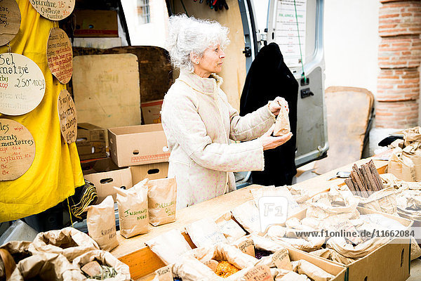 Mature female stall holder selling dried foods at local french market