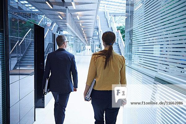 Rückansicht einer Geschäftsfrau und eines Mannes  die durch das Atrium des Büros gehen