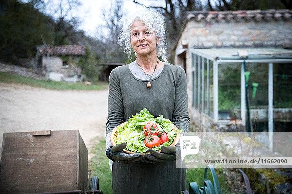 Porträt einer reifen Gärtnerin mit Schale mit Tomaten und Frühlingsgrün