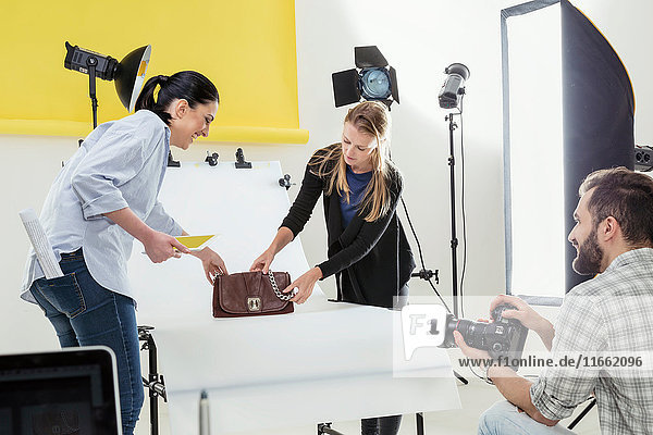 Stylists styling handbag photo shoot in photography studio