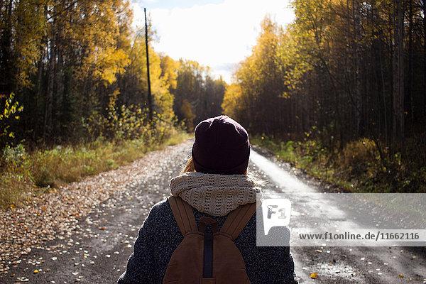 Junge Frau beim Wandern  auf leerer Landstraße  Rückansicht  Gebiet Swerdlowsk  Russland