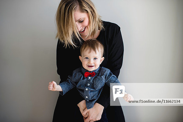 Portrait of male toddler in red bow tie being held by mother
