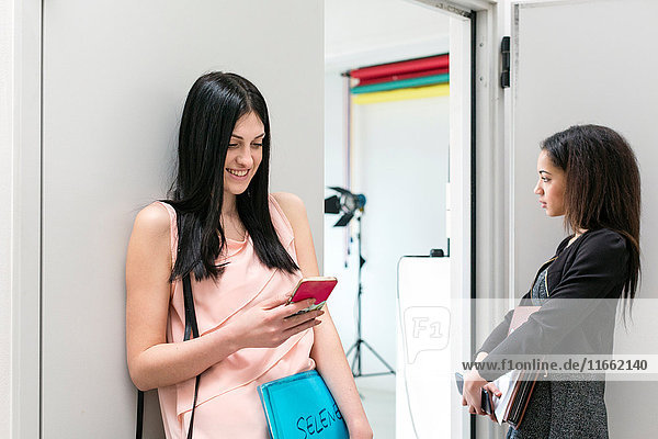Two fashion models waiting by door of photographic studio