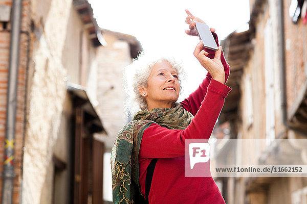 Frau beim Fotografieren auf der Straße  Bruniquel  Frankreich