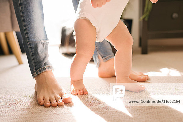 Mother and baby's bare feet on carpet in living room