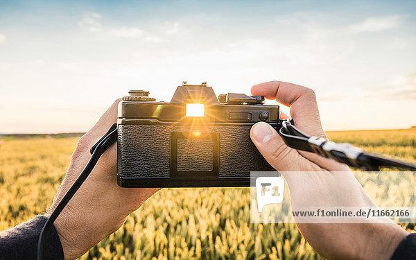 Man standing in field  holding SLR camera  sunlight shining through viewfinder  Neulingen  Baden-Württemberg  Germany