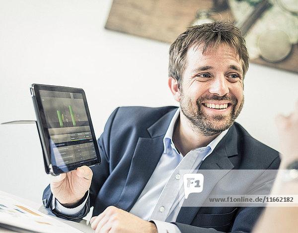 Businessmen at office desk meeting showing digital tablet