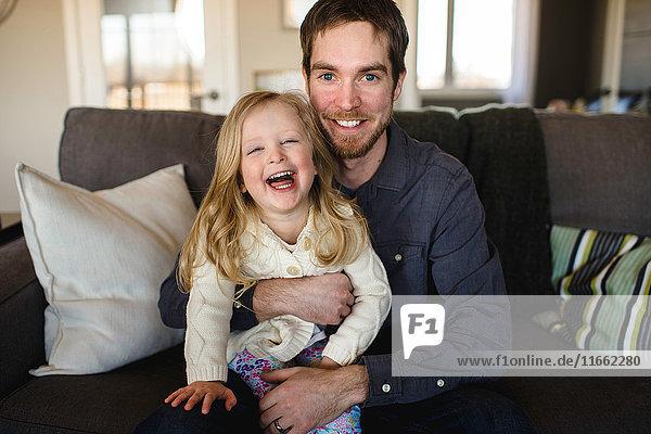 Porträt eines auf dem Sofa sitzenden Mannes mit Tochter auf dem Knie
