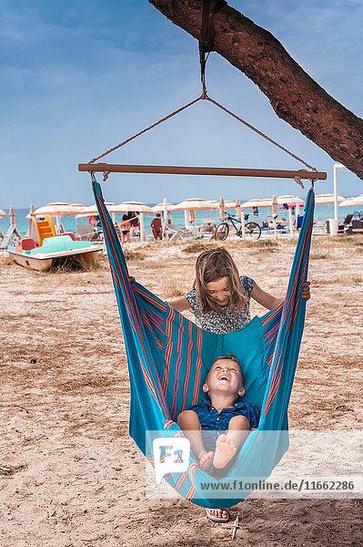 Mädchen schiebt Bruder in Hängematte am Poetto-Strand  Cagliari  Italien
