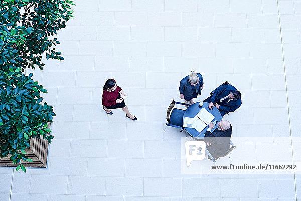 Draufsicht auf Geschäftsleute  die sich im Atrium des Büros treffen