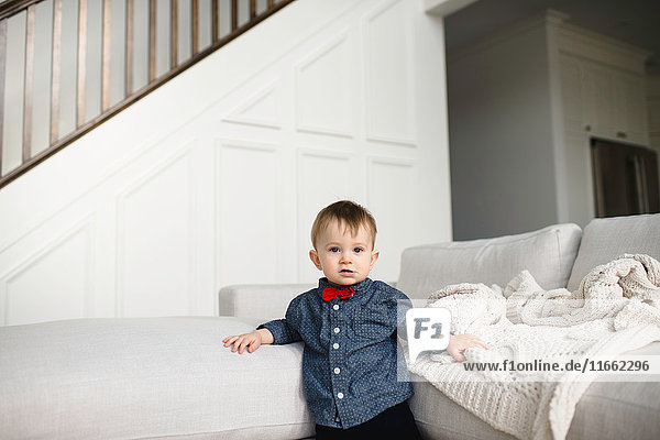 Portrait of male toddler in red bow tie leaning against sofa