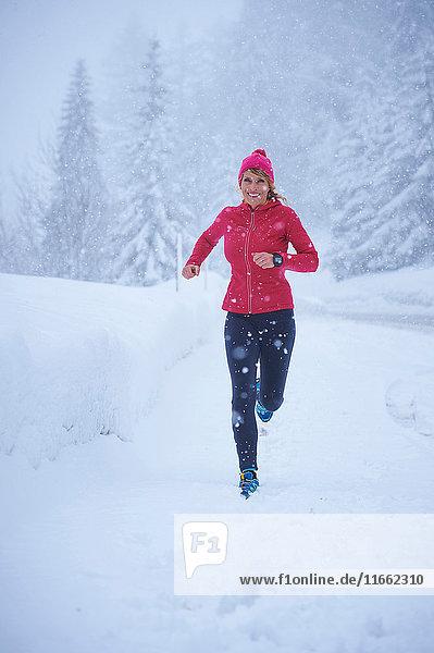 Läuferin läuft bei Schneefall  Gstaad  Schweiz
