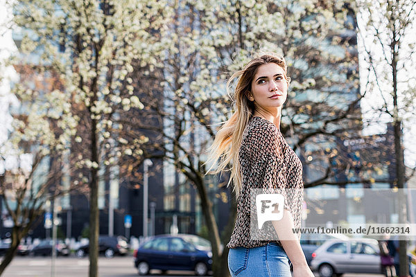 Young woman looking over her shoulder in city
