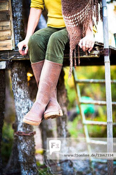 Taille abwärts gerichtete Ansicht einer Frau  die auf einem Baumhaus im Wald sitzt