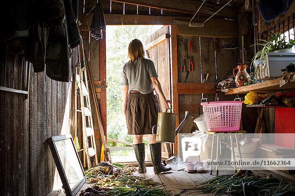 Junge Frau  die eine Gießkanne trägt und aus dem Gartenschuppen hinaussieht