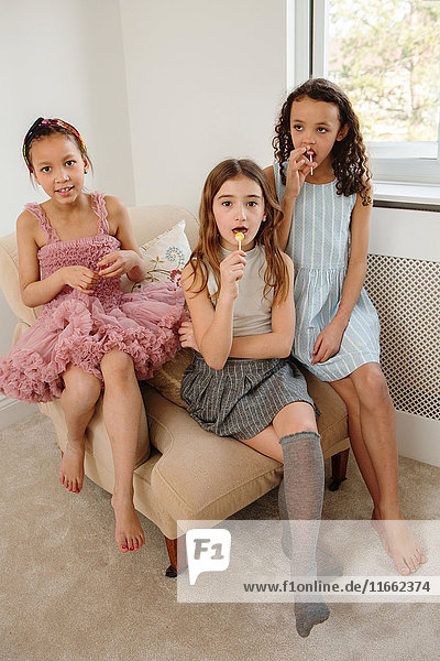 Girls wearing dresses sitting on chair looking at camera
