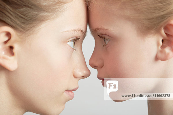 Portrait of two girls  face to face  close-up