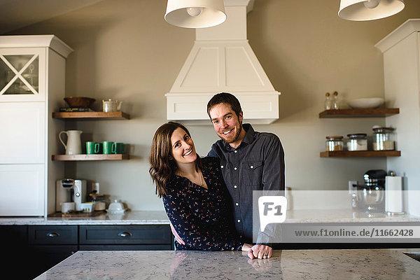Porträt eines Paares mittlerer Erwachsener an der Küchentheke