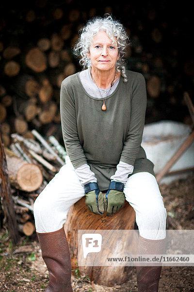 Porträt einer reifen grauhaarigen Frau  die auf einem Baumstamm im Garten sitzt