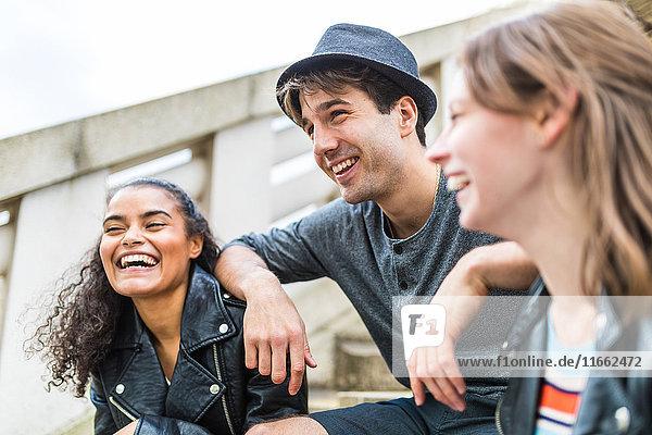 Drei junge erwachsene Freunde auf der Treppe plaudern im Battersea Park