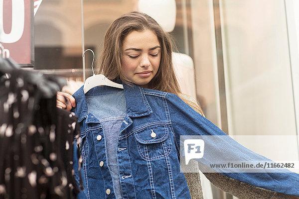 Junge Frau probiert Jeansjacke am Marktstand aus