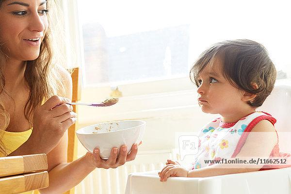 Frau füttert dickköpfiges Mädchen mit Frühstücksflocken