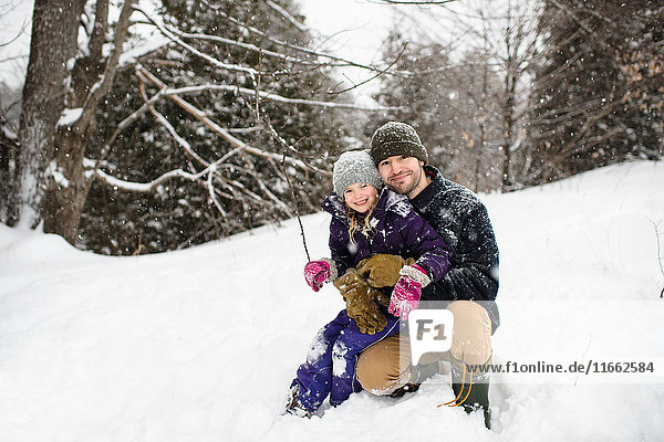 Portrait of mid adult man crouching in snow hugging daughter