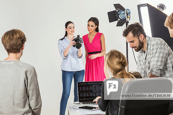 Fashion model and photographer reviewing shoot on digital SLR in photography studio