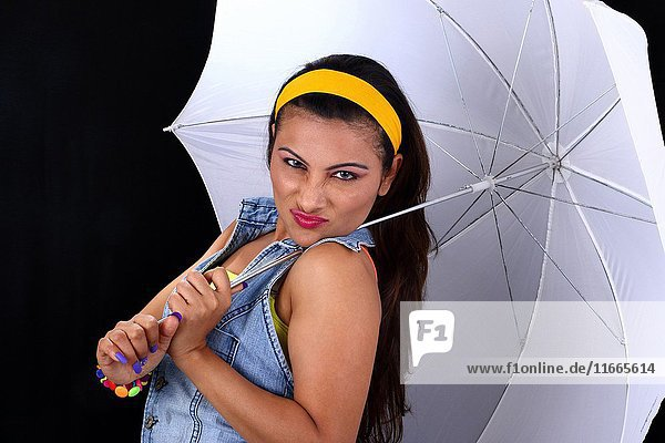 Studio shot of young woman with white umbrella.