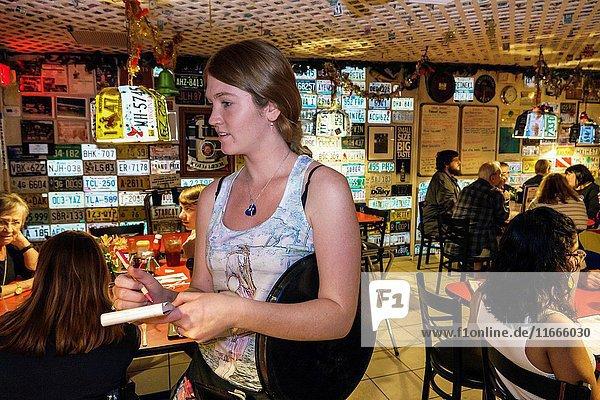 Florida  Key Largo  Upper Florida Keys  Mrs. Mac's Kitchen  restaurant  seafood  dining  interior  decor  license plates  woman  young adult  waitress  writing  order  casual  job  employee